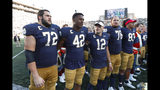Notre Dame's Robert Hainsey (72), Julian Okwara (42), Ian Book (12) and Tommy Kraemer (78) sing after beating New Mexico 66-14 after an NCAA college football game in South Bend, Ind., Saturday, Sept. 14, 2019. (AP Photo/Paul Sancya)