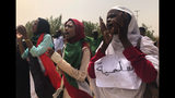 """FILE - In this June 30, 2019 file photo, Sudanese protesters chant slogans as they march during a demonstration against the ruling military council, in Khartoum, Sudan. The sign in Arabic reads, """"peace."""" Sudan's uprising has ushered in a new era both for the nation and for Sudanese women after three decades of autocratic rule by Omar al-Bashir. Sudanese women played a pivotal role in the protests that brought down al-Bashir, and under a joint military-civilian council in power now, they hope for more freedom and equality, and seek to overturn many of the restrictive Islamic laws from the previous era. (AP Photo/Hussein Malla, File)"""