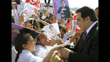 FILE - In this Nov.7, 2008 file photo, children welcome Tunisian President Zine El Abidine Ben Ali as he arrives to a meeting marking the 21st anniversary of his accent to powe in Tunis. Tunisia's autocratic ruler Zine El Abidine Ben Ali, toppled in 2011, died in exile in Saudi Arabia. (AP Photo/Hassene Dridi, File)