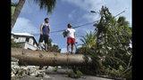 Dos hombres de pie sobre un árbol derribado por el paso del huracán Humberto, en Pitts Bay Road, en Hamilton, Bermuda, el 19 de septiembre de 2019. (AP Foto/Akil J. Simmons)