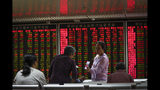 In this Thursday, Sept. 19, 2019, photo, a woman shares a photo on her smartphone with her friends at a brokerage house in Beijing. Asian shares were mostly higher on Friday, Sept. 20, 2019 after a lackluster session on Wall Street, as investors shifted their focus to China-U.S. trade talks after a busy week of central bank news. (AP Photo/Andy Wong)