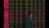 In this Thursday, Sept. 19, 2019, photo, a man walks by an electronic board displaying stock prices at a brokerage house in Beijing. Asian shares were mostly higher on Friday, Sept. 20, 2019 after a lackluster session on Wall Street, as investors shifted their focus to China-U.S. trade talks after a busy week of central bank news. (AP Photo/Andy Wong)