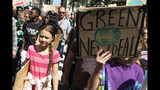 Swedish environmental activist Greta Thunberg, left, takes part during the Climate Strike, Friday, Sept. 20, 2019 in New York. Rallies calling for action on climate change are happening in cities around the world Friday ahead of a summit on the issue. (AP Photo/Eduardo Munoz Alvarez)