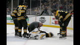 FILE - In this Jan. 19, 2019, file photo, Boston Bruins goaltender Tuukka Rask (40) is attended to on the ice as teammates Zdeno Chara, Brad Marchand (63) and Patrice Bergeron (37) look on after Rask sustained a concussion in a collision with New York Rangers center Filip Chytil during the first period of an NHL hockey game in Boston. The goal counted, Chytil faced no repercussions and Rask was concussed. Those kinds of collisions are happening at an alarming rate over the past couple of seasons, leading to an increase in goaltender concussions. (AP Photo/Mary Schwalm, File)