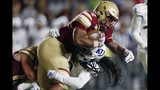 Kansas cornerback Corione Harris, bottom, tackles Boston College running back AJ Dillon during the first half of an NCAA college football game in Boston, Friday, Sept. 13, 2019. (AP Photo/Michael Dwyer)