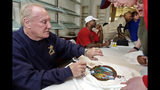"""FILE - In this Jan. 14, 2004, file photo, Howard """"Hopalong"""" Cassady, Heisman Trophy winner from Ohio State in 1955, autographs a Hula Bowl T-shirt for a fan in Kaanapali, Hawaii. Cassady, a Heisman Trophy winner and former NFL running back, died early Friday, Sept. 20, 2019, in Tampa, Fla., Jerry Emig, the Ohio State associate athletic director said. He was 85. Cassady played both football and baseball at Ohio State in the early 1950s, winning the Heisman Trophy in 1955. He also played 10 seasons in the NFL, mostly with the Detroit, and got the nickname """"Hopalong"""" from local sports writers after the black-hatted Western star of the 1950s. (AP Photo/Reed Saxon, File)"""