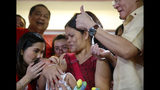 Philippine Health Secretary Francisco Duque III, right, flashes the thumbs up sign shortly after administering anti-polio vaccine to a child during the launch of a campaign to end the resurgence of polio Friday, Sept. 20, 2019 at suburban Quezon city, northeast of Manila, Philippines. Philippine health officials declared a polio outbreak in the country on Thursday, nearly two decades after the World Health Organization declared it to be free of the highly contagious and potentially deadly disease. (AP Photo/Bullit Marquez)