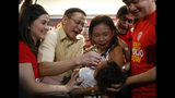 Philippine Health Secretary Francisco Duque III, second from left, administers anti-polio vaccine to a child during the launch of a campaign to end the resurgence of polio Friday, Sept. 20, 2019 at suburban Quezon city, northeast of Manila, Philippines. Philippine health officials declared a polio outbreak in the country on Thursday, nearly two decades after the World Health Organization declared it to be free of the highly contagious and potentially deadly disease. (AP Photo/Bullit Marquez)