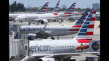 FILE - In this April 24, 2019, photo, American Airlines aircraft are shown parked at their gates at Miami International Airport in Miami. A former American Airlines mechanic who prosecutors say may have some links to terrorists is due to enter a plea to charges that he sabotaged an aircraft with 150 people aboard. An arraignment hearing is set Friday, Sept. 20, 2019, for 60-year-old Abdul-Majeed Marouf Ahmed Alani in Miami federal court. (AP Photo/Wilfredo Lee, File)