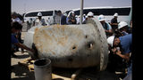 In this photo opportunity during a trip organized by Saudi information ministry, media film holes caused by fragments of a missile in a damaged pipe in the Aramco's Khurais oil field, Saudi Arabia, Friday, Sept. 20, 2019, after it was hit during Sept. 14 attack. Saudi officials brought journalists Friday to see the damage done in an attack the U.S. alleges Iran carried out. Iran denies that. Yemen's Houthi rebels claimed the assault. (AP Photo/Amr Nabil)
