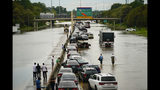 People wait outside of their stranded vehicles along Interstate 10 westbound at T.C Jester, Thursday, Sept. 19, 2019. The freeway is closed because of high water east bound on the freeway. (Mark Mulligan/Houston Chronicle via AP)
