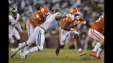Clemson's Travis Etienne, right, rushes out of the tackle of Charlotte's Alex Highsmith, with blocking help from Jackson Carman (79) during the first half of an NCAA college football game Saturday, Sept. 21, 2019, in Clemson, S.C. (AP Photo/Richard Shiro)