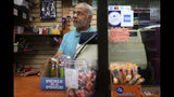 This photo taken Aug. 16, 2019, shows Reginald Stroud, owner of 'Anybody's Dream' convenience store, in Northside, Ohio, standing behind his cash register and a glass barrier while working on Friday. Stroud used to own a home and have a convenience store in the same building on Walnut Street, in downtown Cincinnati, but was displaced when the building was renovated. (Amanda Rossmann/The Cincinnati Enquirer via AP)