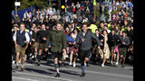 People run to enter the 186th 'Oktoberfest' beer festival in Munich, Germany, Saturday, Sept. 21, 2019. (AP Photo/Matthias Schrader)