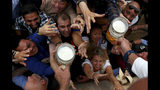 People reach out for a glasses of beer during the opening of the 186th 'Oktoberfest' beer festival in Munich, Germany, Saturday, Sept. 21, 2019. (AP Photo/Matthias Schrader)