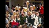 Visitors lift glasses of beer during the opening of the 186th 'Oktoberfest' beer festival in Munich, Germany, Saturday, Sept. 21, 2019. (AP Photo/Matthias Schrader)