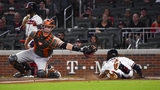 Atlanta Braves' Dansby Swanson scores as San Francisco Giants catcher Buster Posey reaches after a throw from first base during the second inning of a baseball game, Saturday, Sept. 21, 2019, in Atlanta. Max Fried grounded out on the play. (AP Photo/John Amis)