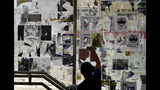 """A pro-China supporter cleans up posters and labels with messages on a """"Lennon Wall"""" of anti-government posters at Causeway Bay in Hong Kong, Saturday, Sept. 21, 2019. The original """"Lennon Wall"""" was first created in Prague after the assassination of Beatles band member John Lennon. It was covered with art, notes as well as lyrics from The Beatles music. (AP Photo/Vincent Yu)"""