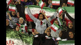 """FILE - In this Oct. 16, 2018 file photo, Iranian women cheer as they wave their country's flag after authorities in a rare move allowed a select group of women into Azadi stadium to watch a friendly soccer match between Iran and Bolivia, in Tehran, Iran. Sahar Khodayari, an Iranian female soccer fan died after setting herself on fire outside a court after learning she may have to serve a six-month sentence for trying to enter a soccer stadium where women are banned, a semi-official news agency reported Tuesday, Sept. 10, 2019. The 30-year-old was known as the """"Blue Girl"""" on social media for the colors of her favorite Iranian soccer team, Esteghlal. (AP Photo/Vahid Salemi, File)"""