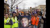 FILE - In this March 11, 2015 file photo, Brandon Marshall carries a photo of Anthony Hill as protesters march through the street demonstrating Hill's shooting death by a police officer, in Decatur, Ga. Robert Olsen, then a DeKalb County police officer, shot and killed 27-year-old Anthony Hill in March 2015. Olsen was indicted on charges including felony murder. Jury selection for his trial is scheduled to start Monday, Sept. 23, 2019. (AP Photo/David Goldman, File)
