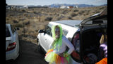 """Alex Clark smokes a cigarette outside of the Storm Area 51 Basecamp event Friday, Sept. 20, 2019, in Hiko, Nev. The event was inspired by the """"Storm Area 51"""" internet hoax. Thousands of curious Earthlings from around the globe traveled to festivals, and several hundred made forays toward the secret Area 51 military base in the Nevada desert on Friday, drawn by an internet buzz and a social media craze sparked by a summertime Facebook post inviting people to """"Storm Area 51."""" (AP Photo/John Locher)"""