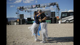 """Lizbeth Donnelly, left, kisses Jason Donnelly as they dance at the Storm Area 51 Basecamp event Friday, Sept. 20, 2019, in Hiko, Nev. The event was inspired by the """"Storm Area 51"""" internet hoax. Thousands of curious Earthlings from around the globe traveled to festivals, and several hundred made forays toward the secret Area 51 military base in the Nevada desert on Friday, drawn by an internet buzz and a social media craze sparked by a summertime Facebook post inviting people to """"Storm Area 51."""" (AP Photo/John Locher)"""