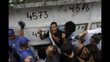 An uncle of 8-year-old Ágatha Sales Félix shouts and cries during her burial at the cemetery in Rio de Janeiro, Brazil, Sunday, Sept. 22, 2019. Félix was hit by a stray bullet Friday amid what police said was a shootout with suspected criminals. However, residents say there was no shootout, and blame police. (AP Photo/Silvia Izquierdo)