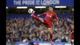 Liverpool's Roberto Firmino reaches for the ball during the British premier League soccer match between Chelsea and Liverpool, at the Stamford Bridge Stadium, London, Sunday, Sept. 22, 2019. (AP Photo/Matt Dunham)