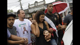 Vanessa Francisco Sales, carrying a doll that belonged to her 8-year-old daughter Ágatha Sales Felix, holds the hand of her husband Adegilson Felix, second from left, as they walk in their daughter's funeral procession to the cemetery in Rio de Janeiro, Brazil, Sunday, Sept. 22, 2019. Félix was hit by a stray bullet Friday amid what police said was shootout with suspected criminals. However, residents say there was no shootout, and blame police. (AP Photo/Silvia Izquierdo)