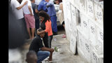 The uncle of the late 8-year-old Ágatha Sales Felix cries during her burial at the cemetery in Rio de Janeiro, Brazil, Sunday, Sept. 22, 2019. Félix was hit by a stray bullet Friday amid what police said was shootout with suspected criminals. However, residents say there was no shootout, and blame police. (AP Photo/Silvia Izquierdo)