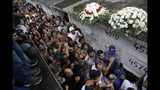 Relatives and friends applaud in honor of the late 8-year-old Ágatha Sales Felix, who was hit by a a stray bullet, as they bury her at the cemetery in Rio de Janeiro, Brazil, Sunday, Sept. 22, 2019. Félix was hit by a stray bullet Friday amid what police said was shootout with suspected criminals. However, residents say there was no shootout, and blame police. (AP Photo/Silvia Izquierdo)