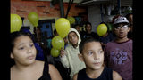 Youths attend a protest and gathering in memory of the late 8-year-old Ágatha Sales Félix, whose photo of her clutching a yellow balloon is circulating online, as residents demand an end to the violence in the Alemao complex slum of Rio de Janeiro, Brazil, Sunday, Sept. 22, 2019. Félix was hit by a stray bullet Friday amid what police said was shootout with suspected criminals. However, residents say there was no shootout, and blame police. (AP Photo/Silvia Izquierdo)