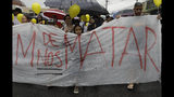 "Protesters with yellow balloons carry a banner that reads in Portuguese: ""Stop killing us"" during a gathering in memory of the late 8-year-old Ágatha Sales Félix, whose photo of her clutching a yellow balloon is circulating online, as people demand an end to the violence in the Alemao complex slum of Rio de Janeiro, Brazil, Sunday, Sept. 22, 2019. Félix was hit by a stray bullet Friday amid what police said was shootout with suspected criminals. However, residents say there was no shootout, and blame police. (AP Photo/Silvia Izquierdo)"