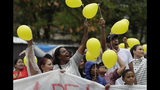 People hold up yellow balloons during a gathering in memory of the late 8-year-old Ágatha Sales Félix, whose photo of her clutching a yellow balloon is circulating online, as residents demand an end to the violence in the Alemao complex slum of Rio de Janeiro, Brazil, Sunday, Sept. 22, 2019. Félix was hit by a stray bullet Friday amid what police said was shootout with suspected criminals. However, residents say there was no shootout, and blame police. (AP Photo/Silvia Izquierdo)