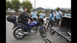 Wilson Sandoval, left, the team manager of the Esteban Chaves Foundation, talks to his cyclists after a training session in Puente Piedra near Bogota, Colombia, Friday, Sept. 13, 2019. Sandoval said his teams require any aspiring cyclist that wants a tryout to take an obligatory doping test. (AP Photo/Fernando Vergara)
