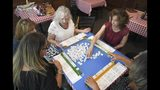 Michelle Tishler, top right, leads a game of mahjong with friends at Corner Pub in the Woods in Bellevue, Tenn. on Sept. 4, 2019. Tishler, who learned mahjong from the women in her family, also teaches the game. (Shelley Mays/The Tennessean via AP)