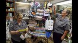 "In this Aug. 20, 2019 photo, Ethel Ford, left, and Nannette Wall hang their bags made of plastic grocery bags on a display in the gift shop of the Fishing Museum o at the Sebastian Inlet State Park in Sebastian, Fla.. Dubbed the ""Recycling Grannies"" by park staff, Ford and Wall were given space in the gift shop to sell their creations with all the proceeds going back to the park. (Patrick Dove/TCPalm.com via AP)"