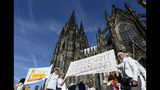Protesters build a human chain in front of the Cologne Cathedral in Cologne, Germany, Sunday, Sept. 22, 2019. About 800 people have protested for more gender equality in the Catholic Church in Germany. (Roberto Pfeil/dpa via AP)