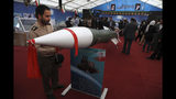 """An Iranian army member looks at a missile in an exhibition in which the Revolutionary Guard also displays pieces of the American drone Global Hawk shot down by the Guard in the Strait of Hormuz in June 2019, in Tehran, Iran, Saturday, Sept. 21, 2019. Iran's powerful Revolutionary Guard is ready for combat and """"any scenario,"""" its chief commander said Saturday, as the country's nuclear deal with world powers collapses and the U.S. alleged Iran was behind a weekend attack on major oil sites in Saudi Arabia that shook global energy markets. (AP Photo/Vahid Salemi)"""