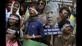 Pakistan children dress up like injured Kashmiri children and hold a portrait of U.S. President Donald Trump during a demonstration organized by International Human Right Movement to express solidarity with Indian Kashmiris, in Lahore, Pakistan, Sunday, Sept. 22, 2019. Tensions between Pakistan and India, two nuclear-armed countries, has increased since Aug. 5, when India downgraded the autonomy of its side of Kashmir and imposed tighter controls on the area. (AP Photo/K.M. Chaudary)