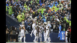 Seattle Seahawks fans, background, in rain gear watch quietly as New Orleans Saints celebrate a touchdown on a fumble recovery by Vonn Bell, third right, during the first half of an NFL football game Sunday, Sept. 22, 2019, in Seattle. (AP Photo/Ted S. Warren)