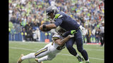 Seattle Seahawks quarterback Russell Wilson, right, scores a touchdown on a run as New Orleans Saints' Marshon Lattimore tries to stop him during the second half of an NFL football game, Sunday, Sept. 22, 2019, in Seattle. (AP Photo/Ted S. Warren)