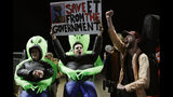 """Mario Rayna, center, chants with others at an entrance to the Nevada Test and Training Range near Area 51 Friday, Sept. 20, 2019, near Rachel, Nev. People gathered at the gate inspired by the """"Storm Area 51"""" internet hoax. (AP Photo/John Locher)"""