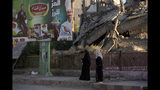 In this Thursday, Sept. 5, 2019, photo, two women walk past a billboard and a destroyed building in al-Naim square, used by Islamic State militants for execution during their rule, in Raqqa, Syria. Officials say more than 800,000 people have returned to the city and its adjacent suburbs_ nearly eight times the residents left when the militants were finally expelled in Oct. 2017. (AP Photo/Maya Alleruzzo)