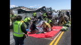 In this photo released by the Garfield County Sheriff's Office, Emergency Medical Services personnel assist victims of a bus crash near Bryce Canyon National Park in southern Utah, Friday, Sept. 20, 2019. (Sheriff Danny Perkins/Garfield County Sheriff's Office via AP)