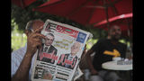 "A man reads Al-Shorouk daily newspaper showing candidates Kais Saied, right, ) and Nabil Karoui on its front-page, a day after the first round of presidential elections, in a coffee shop in Tunis, Tunisia, Monday, Sept. 16, 2019. A polling firm projected Sunday that an independent outsider candidate and a jailed media magnate will head to Tunisia's presidential runoff, after a roller coaster, 26-candidate election. Headline in Arabic reads ""Political earthquake"". (AP Photo/Mosa'ab Elshamy)"