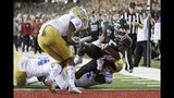 Washington State wide receiver Travell Harris, right, scores a touchdown as he is brought down by UCLA linebacker Krys Barnes, second from right, and defensive back Jay Shaw, left, in front of Rayshad Williams during the first half of an NCAA college football game in Pullman, Wash., Saturday, Sept. 21, 2019. (AP Photo/Young Kwak)