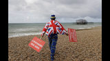 Anti Brexit campaigner Steve Bray walks on the beach to pose for a photograph during the Labour Party Conference at the Brighton Centre in Brighton, England, Monday, Sept. 23, 2019. (AP Photo/Kirsty Wigglesworth)