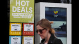 A woman walks past a closed Thomas Cook travel shop in London, Monday, Sept. 23, 2019. British tour company Thomas Cook collapsed early Monday after failing to secure emergency funding, leaving tens of thousands of vacationers stranded abroad. (AP Photo/Frank Augstein)