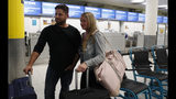 John Garret and Ajouline Chaffee from Boston Ma., who were supposed to be flying to Malta, speak to the media near the empty Thomas Cook check in desks in Gatwick Airport, England Monday, Sept. 23, 2019. British tour company Thomas Cook collapsed early Monday after failing to secure emergency funding, leaving tens of thousands of vacationers stranded abroad. (AP Photo/Alastair Grant)